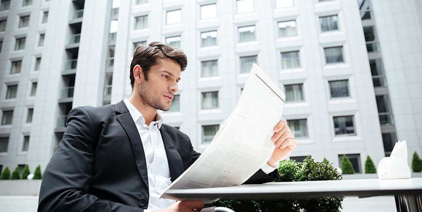 Businessman reading newspaper in outdoor cafe