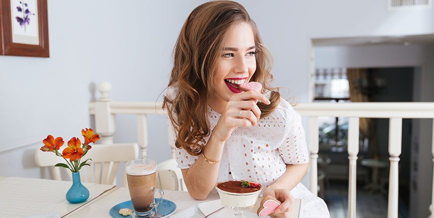 Cheerful attractive young woman sitting and eating heart shaped cookies