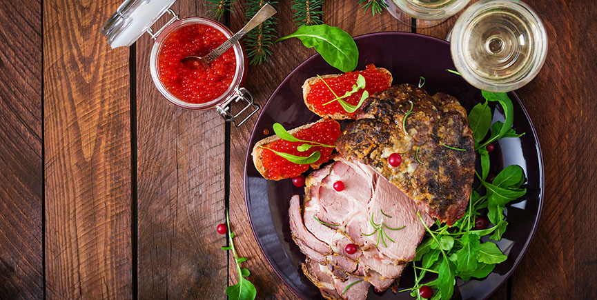 Christmas baked ham and red caviar, served on the old wooden tab