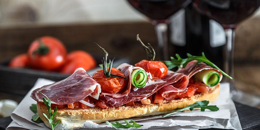 Close up bruschetta with proschuto, tomato, parmesan cheese and arugula