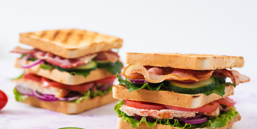 Club sandwich with chicken breast, bacon, tomato, cucumber and h