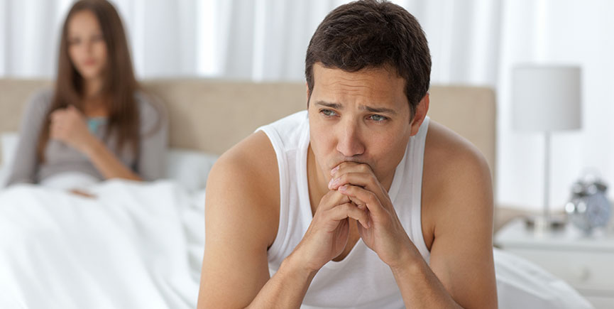 Pensive man having a headache sitting on the bed