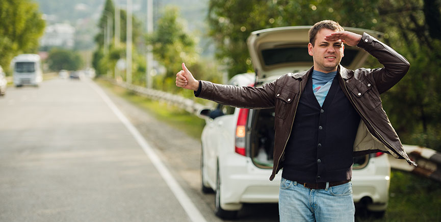 Happy man hitchhiking by a broken car on the road