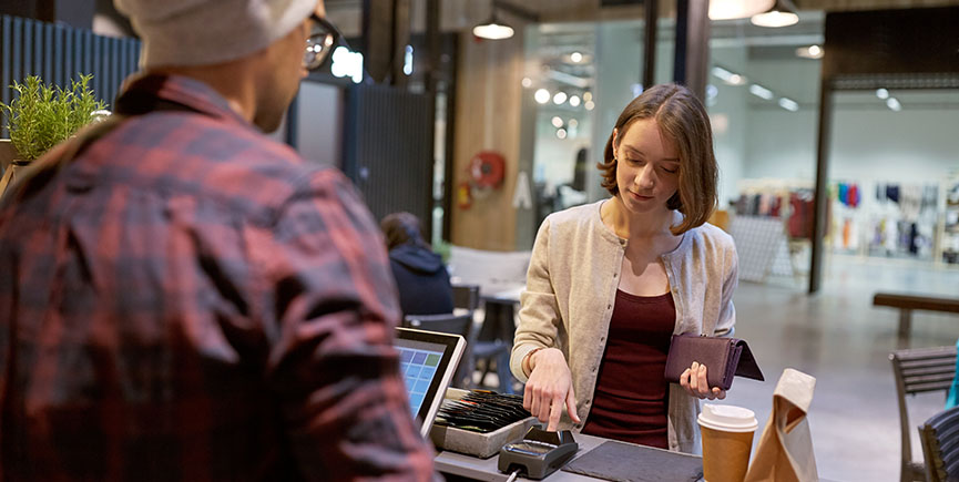 happy woman paying for purchases at cafe