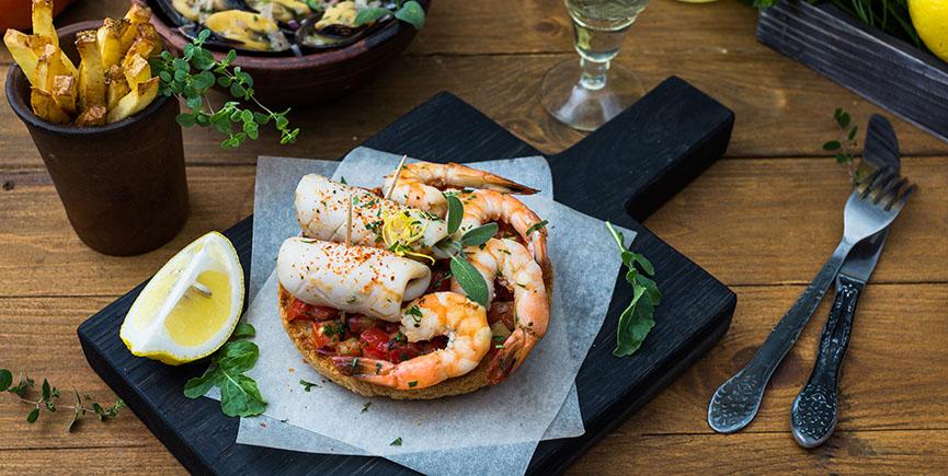 Italian food. Bruschetta with squid and prawns, tomatoes, parsley.