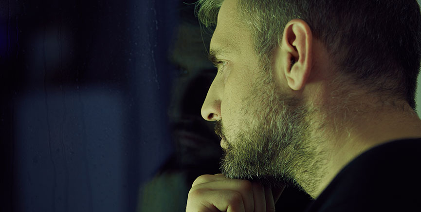 Man thinking and looking through the window