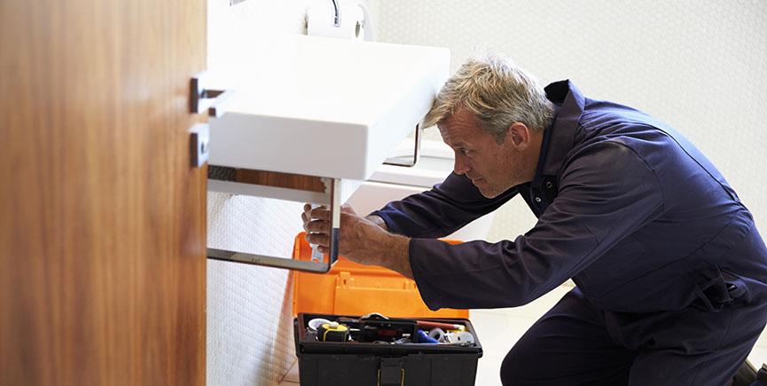 Plumber Working On Sink In Bathroom