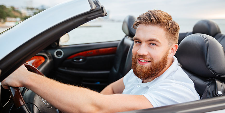 Portrait of young handsome smiling man in his own car