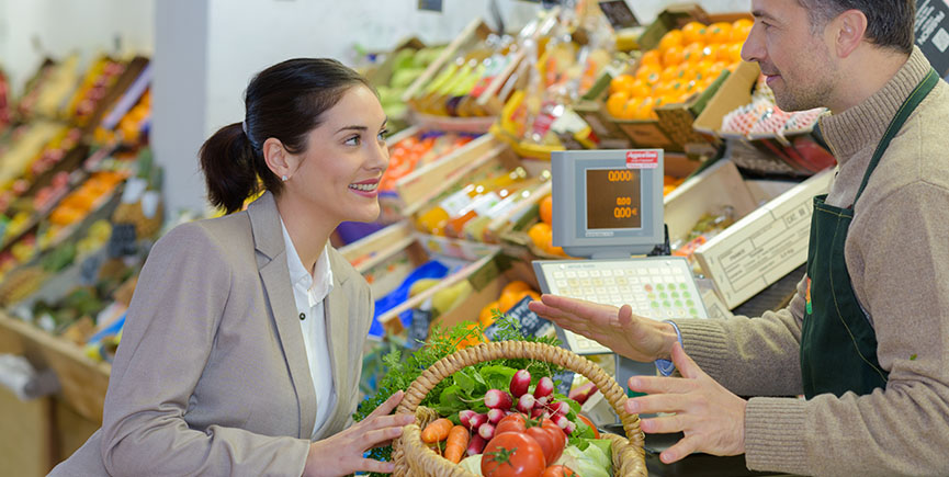 smiling woman choosing different fruits at farm food store displ