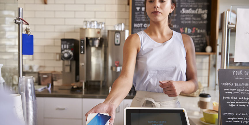 Waitress at coffee shop taking card payment from a customer